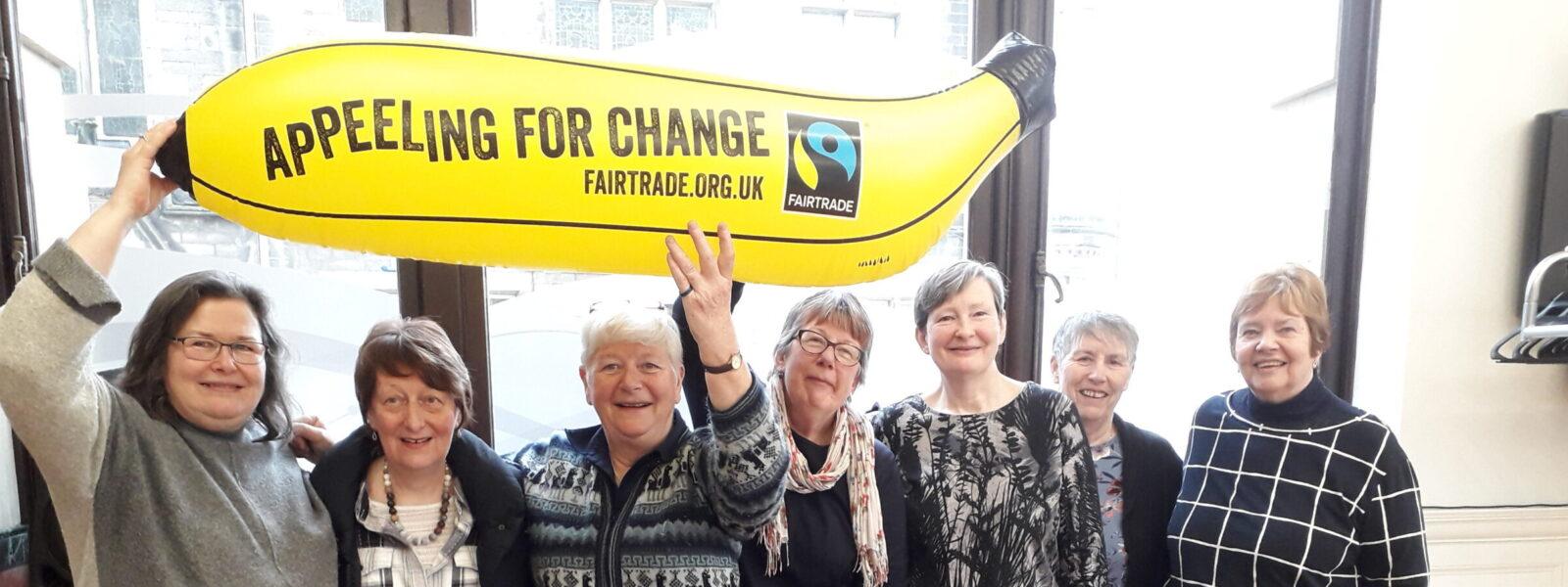 A group of women showing a banana balloon to promote Fairtrade